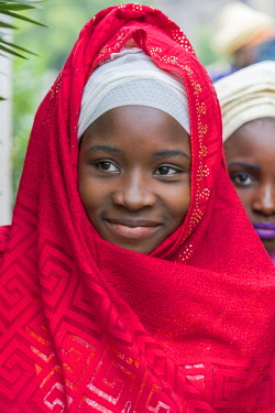 NGR1069 Nigeria, Kano State, Kano. A Hausa girl dressed in a brilliant red shawl.