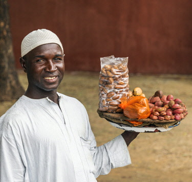 NGR1073 Nigeria, Kano State, Kano. A street vendor with reddish Kola nuts on his tray and bitter Kolas in the plastic bag.  The nut contains caffeine. It has important cultural significance to many ethnic gro...
