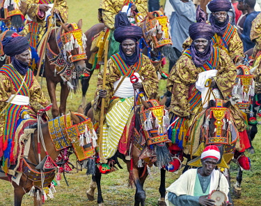 NGR1086 Nigeria, Kano State, Kano. Hausa men dressed in bright-coloured flowing robes and indigo turbans participate in a Durbar parade.  Their fine horses are equally impressive, adorned with ornate ceremoni...