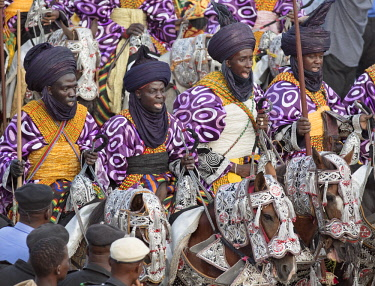 NGR1097 Nigeria, Kano State, Kano. Hausa men dressed in bright-coloured purple flowing robes and indigo turbans participate in a Durbar parade.  Their fine horses are equally impressive, adorned with ornate c...