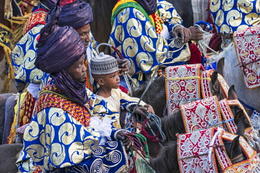 NGR1103 Nigeria, Kano State, Kano. An awestruck young boy accompanies his father and other Hausa horsemen on a Durbar parade.  Their bright-coloured flowing robes and indigo turbans are matched by their equal...