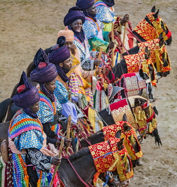 NGR1111 Nigeria, Kano State, Kano. Hausa men dressed in bright-coloured flowing robes and indigo turbans participate in a Durbar parade.  Their fine horses are equally impressive, adorned with ornate ceremoni...