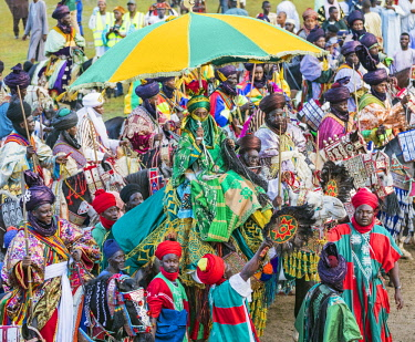 NGR1118 Nigeria, Kano State, Kano. The Emir of Kano resplendent in brilliant green robes attends a Durbar parade riding on a white camel.  A servant holds up a large umbrella to shade him from the sun while t...