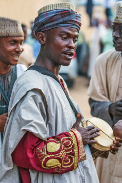 NGR1124 Nigeria, Kano State, Kano. A Hausa drummer plays a traditional hour-glass shaped talking drum known to the Hausa as kalangu. They are amongst West Africa's oldest musical instruments.