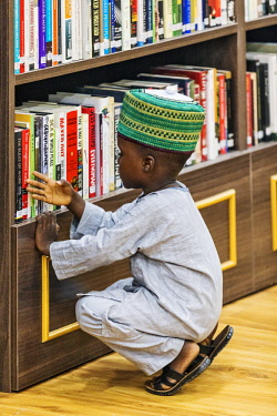 NGR1125 Nigeria, Kano State, Kano. A young Hausa boy counts books in the Emir of Kano's palace library.