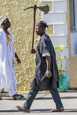 NGR1128 Nigeria, Kano State, Kano. A Hausa man carries an old battle-axe in the grounds of Government House in Kano as a part of the Durbar celebrations.