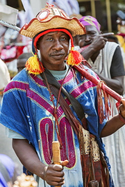 NGR1135 Nigeria, Kano State, Kano. A Hausa man in an embroidered robe and Fulani-style hat carries a large cleaver during a Durbar celebration at Government House in Kano.