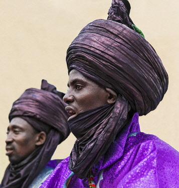 NGR1141 Nigeria, Kano State, Kano. Two Hausa men in colourful purple robes and indigo turbans sing during a Durbar celebration.