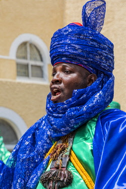 NGR1148 Nigeria, Kano State, Kano. A Hausa man wearing a brilliant blue turban sings while mounted on his horse during a Durbar celebration at Government House in Kano.