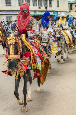 NGR1157 Nigeria, Kano State, Kano. Hausa horsemen in flowing robes and colourful turbans ride through the streets of Kano on their beautifully adorned horses during a Durbar celebration.