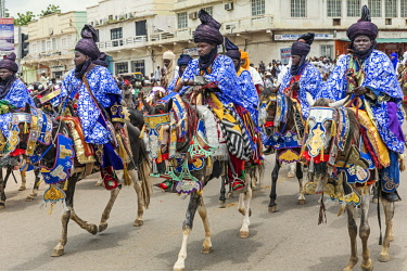 NGR1158 Nigeria, Kano State, Kano. Hausa horsemen in flowing blue robes and indigo turbans ride through the streets of Kano on their beautifully adorned horses during a Durbar celebration.