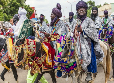 NGR1159 Nigeria, Kano State, Kano. Hausa horsemen in flowing robes and indigo turbans ride through the streets of Kano on their beautifully adorned horses during a Durbar celebration.
