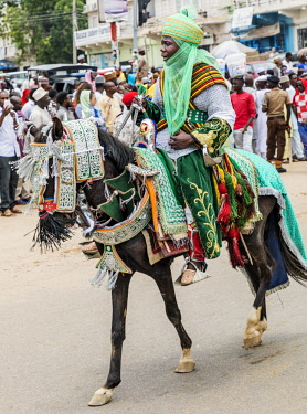 NGR1161 Nigeria, Kano State, Kano. A Hausa horsemen in flowing robes and green turban rides through the streets of Kano on his beautifully adorned horse during a Durbar celebration.