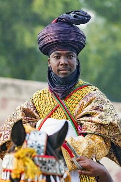 NGR1162 Nigeria, Kano State, Kano. An elegant Hausa man in flowing robes and indigo turban rides his horse during a Durbar celebration.
