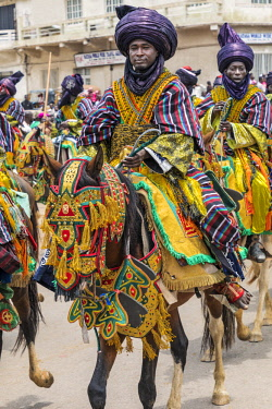 NGR1164 Nigeria, Kano State, Kano. Hausa horsemen in flowing robes and indigo turbans ride through the streets of Kano on their beautifully adorned horses during a Durbar celebration.