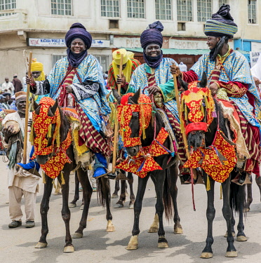 NGR1165 Nigeria, Kano State, Kano. Hausa horsemen in flowing blue robes and indigo turbans ride through the streets of Kano on their beautifully adorned horses during a Durbar celebration.