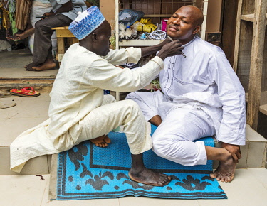 NGR1166 Nigeria, Kano State, Kano. A barber shaves his client in a narrow street in the sprawling 15th century Kurmi market.