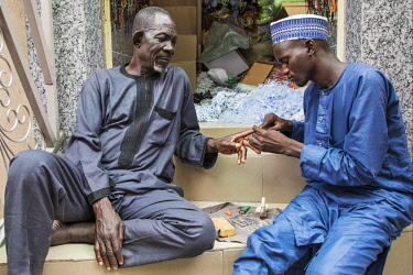 NGR1167 Nigeria, Kano State, Kano. A manicurist cuts the nails of his client in a narrow street in the sprawling 15th century Kurmi market.