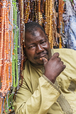 NGR1168 Nigeria, Kano State, Kano. A shopkeeper relaxes beside the coloured prayer beads he is offering for sale at his shop in the sprawling 15th century Kurmi market.