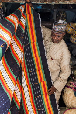 NGR1170 Nigeria, Kano State, Kano. A shopkeeper displays bright locally woven cotton material in the sprawling 15th century Kurmi market. Narrow looms are trditionally used necessitating many hand-sewn joins...