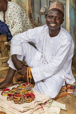 NGR1171 Nigeria, Kano State, Kano. A street vendor offers beaded bracelets for sale in the sprawling 15th century Kurmi market.