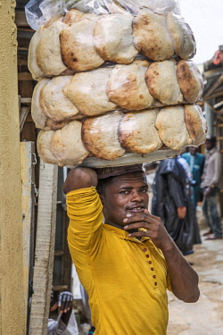 NGR1172 Nigeria, Kano State, Kano. A man takes locally-baked flat bread from the bakery to sell to customers in the sprawling 15th century Kurmi market.