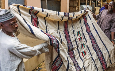 NGR1173 Nigeria, Kano State, Kano. Two men display attractive locally woven cotton material in the sprawling 15th century Kurmi market. Narrow looms are trditionally used necessitating many hand-sewn joins to...