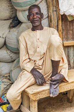 NGR1174 Nigeria, Kano State, Kano. A shopkeeper relaxes outside his shop in the sprawling 15th century Kurmi market.