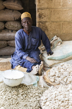 NGR1175 Nigeria, Kano State, Kano. A man sits outside a shop selling potash in the sprawling 15th century Kurmi market. Potash is used to prepare a number of local dishes and in soup.  It is next in importanc...