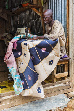 NGR1176 Nigeria, Kano State, Kano. A tailor sews an attractive round leather rug at the entrance to his worshop in the sprawling 15th century Kurmi market.