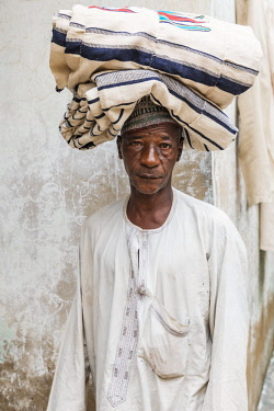 NGR1178 Nigeria, Kano State, Kano. A man carries a bolt of locally woven cotton cloth on his head in the sprawling 15th century Kurmi market.