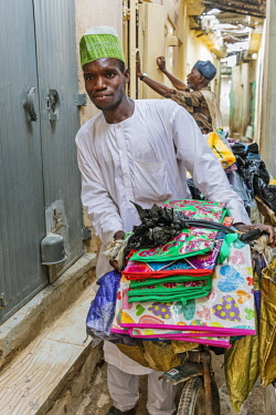 Nigeria, Kano State, Kano. A man negotiates a way through the narrow alleyways of the sprawling 15th century Kurmi market with a bicycle laden with goods to sell.