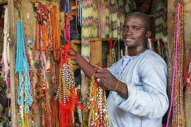 NGR1180 Nigeria, Kano State, Kano. A shopkeeper displays strings of beads at his small shop in the sprawling 15th century Kurmi market.
