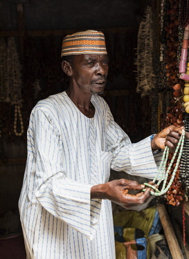 NGR1181 Nigeria, Kano State, Kano. A shopkeeper offers a customer a string of old beads at his small shop in the sprawling 15th century Kurmi market.
