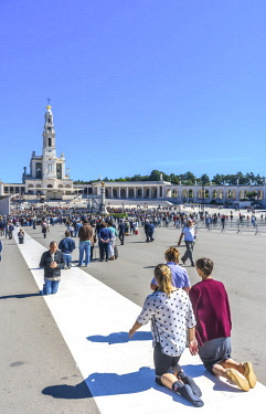 EU23WPE0072 Kneeling pilgrims attending 100th Anniversary of Apparitions Celebration. Basilica of our Lady of the Rosary, Fatima, Portugal. Church created on site where on May 13th three Portuguese shepherd child...