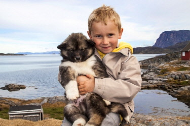 GR01MGL0031 Greenland, Nuuk, Sermersooq. Local boy holds his Siberian Husky puppy