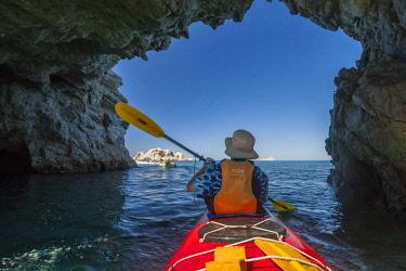 SA13BJY0209 Mexico, Baja California Sur, Isla San Jose. Ocean kayaker passing through rock tunnel