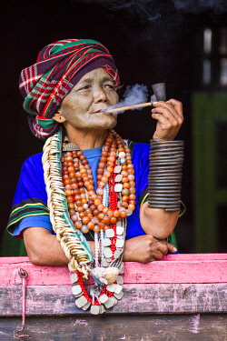 MYA2438 Myanmar, Mindat. A Chin lady with traditional tattoed face, smoking her pipe.