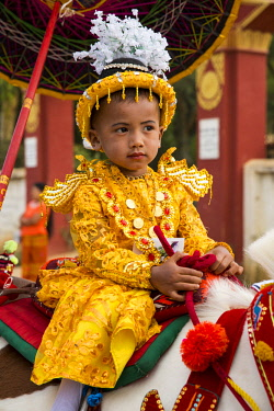 MYA2416 Myanmar, Bagan. A young boy riding a horse during a ceremony in which the boy is inducted as a novice Buddhist monk.