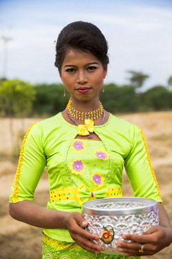 MYA2417 Myanmar, Bagan. A young woman holding a silver alms bowl.