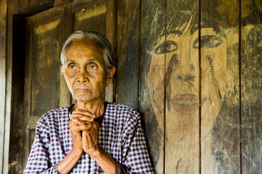 MYA2403 Myanmar, Mrauk U. A lady of the Chin people with traditional tattooed face, standing in front of a painting on the wall of her home, in a small village up river from Mrauk U.