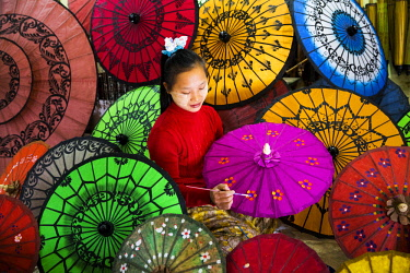 MYA2366 Myanmar, Mandalay. A young lady painting paper umbrellas in a shop in Mandalay.