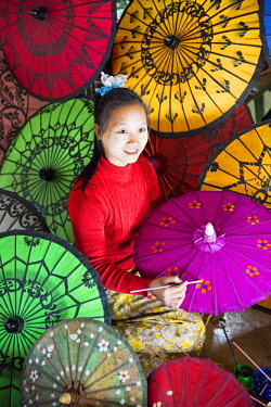 MYA2367 Myanmar, Mandalay. A young lady painting paper umbrellas in a shop in Mandalay.