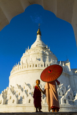 MYA2361 Myanmar, Mingun. A young monk and a nun at the white Hsinbyume Pagoda on the banks of the Irrawaddy.