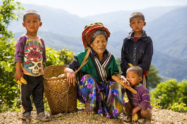 Myanmar, Mindat. A Chin lady with traditional tattoed face, and her three sons.
