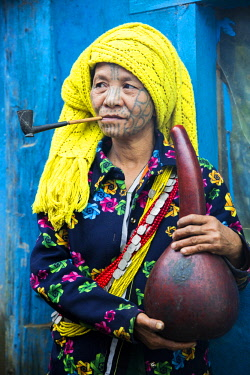 Myanmar, Mindat. A Chin lady with traditional tattoed face, smoking her pipe and holding a water gourd.