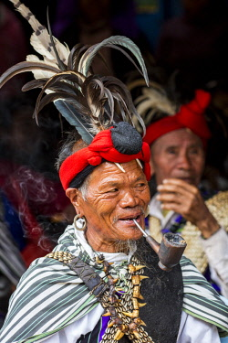 Myanmar, Mindat. A senior member of the Mindat community dressed in his finery at a funeral.