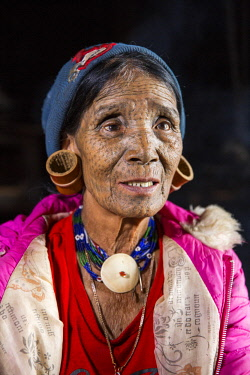 Myanmar, Mindat. A Chin lady with traditional tattoed face, and large bamboo earrings.