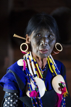 Myanmar, Mindat. A Chin lady with traditional tattoed face, and large bamboo ear-rings.