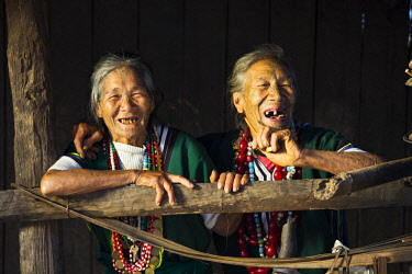MYA2221 Myanmar, Mindat. Two Chin ladies with traditional tattoed faces, enjoying a joke.